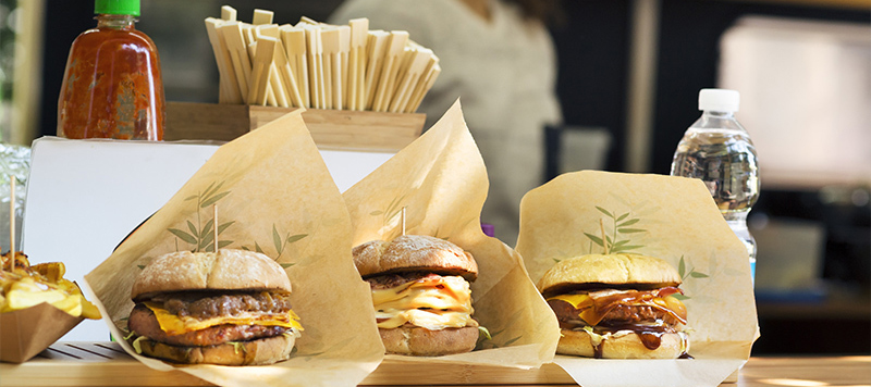 To-go burgers are prominently displayed in a food truck window along with a bottle of water.